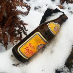 Bierflasche am Waldrand im Schnee